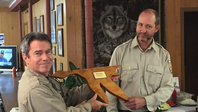 Kevin Sloan accepts a plaque, signed by refuge employees, from Bob Leffel, deputy project leader at Chincoteague National Wildlife Refuge. Sloan, project leader at the refuge, is retiring after three decades in government service.
