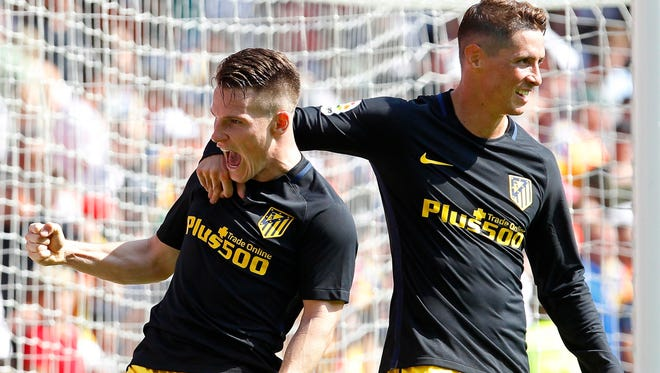 Atletico Madrid's French striker Kevin Gameiro (L) celebrates with his teammate Fernando Torres (R) after scoring the 2-0 lead during the Spanish Primera Division soccer match between Valencia CF and Atletico Madrid.