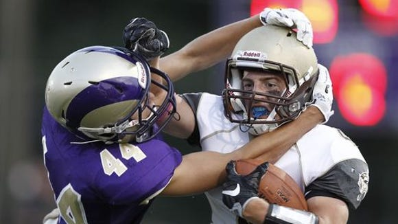 Clarkstown South's Kyle Samuels (4) is tackled by Clarkstown