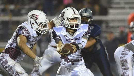 Scarsdale's Barry Klein hands off to Nick Leone during Friday's game against John Jay High School.