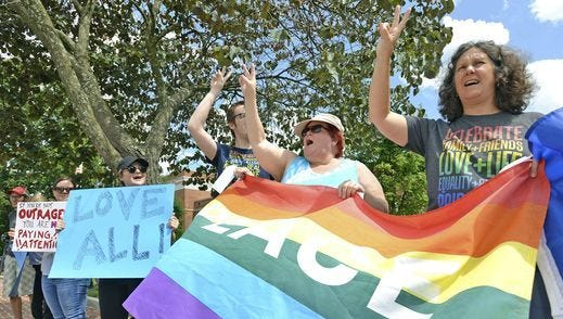 Laura Hainsworth, right, and Kristina Morris wave peace signs while holding a rainbow colored PEACE flag during a counter protest to the rally in Charlottesville, Va. on Aug. 12, 2017, in Abingdon, Va.