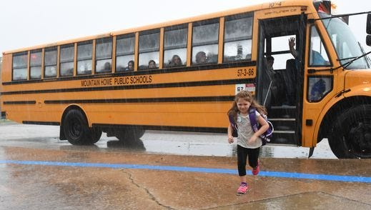 A Mountain Home kindergarten student runs through the pouring rain Tuesday on her first day of school. The district will survey parents regarding a program that would extend school hours for K-2 students.