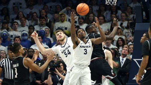 Xavier's Quentin Goodin (3) and Cincinnati's Trevon Scott battle for a rebound in Saturday's 89-76 XU win. The Musketeers dominated the boards 44-27, against a UC team that had led the nation in rebound margin.