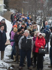 Several hundred people line up on St. Paul Street to