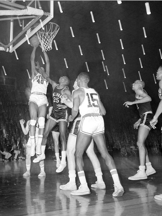 FILE - In this March 23, 1963, file photo, Loyola's Vic Rouse (40) leaps to score in the closing seconds of overtime against Cincinnati to win 60-58 in the National Collegiate basketball finals, March 23, 1963, Louisville, Ky. The Ramblers play Nevada on Thursday, March 22, 2018, after two thrilling wins to reach the Sweet 16, earning more wins this season than the team that won the 1963 title. (AP Photo/File)