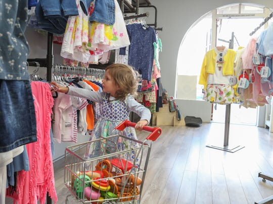 Caroline McDaniel pushes her cart through Jadabug's Kids Boutique while shopping with her mother in this file photo from  February 23, 2018. When the La Quinta store, owned by Heidi McArthur, reopens after being closed over two months as a result of the novel coronavirus pandemic, customers will need to wear face coverings, sanitize their hands and practice safe-distancing of at least 6 feet from other customers.