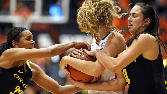 Oregon's Lexi Petersen, left, and Maite Cazorla, right, try to steal the ball from Oregon State's Katie McWilliams, center, in the first half of an NCAA college basketball game, in Corvallis, Ore., on Friday, Jan. 8, 2016. (AP Photo/Timothy J. Gonzalez)