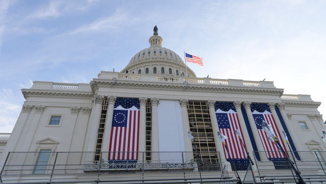 Flags are installed on the west front during the dress rehearsal for the 58th Presidential Inauguration at the U.S. Capitol.
