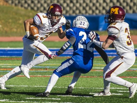 Madison ballcarrier Nasir Love (3) tries to get past Millburn defender Griffin Titan (22) at the 85th annual, and final Madison Millburn Thanksgiving Day football game, at Millburn, November 23, 2017.