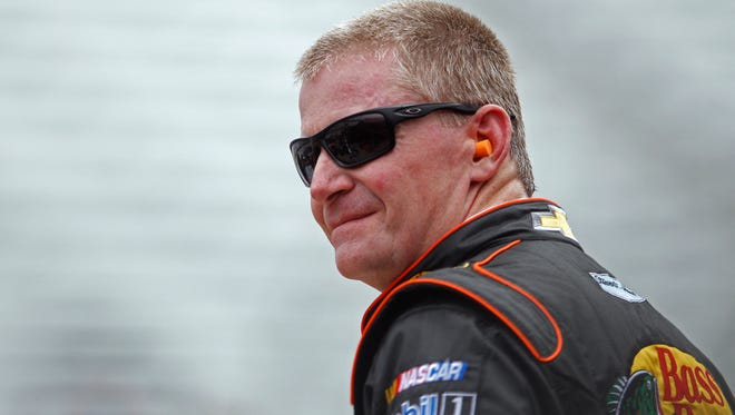Driver Jeff Burton watches from the wall as his crew works on his car during practice for the Irwin Tools Night Race NASCAR Sprint Cup Series auto race at Bristol Motor Speedway on Friday, Aug. 22, 2014, in Bristol, Tenn.