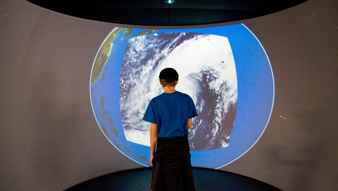 A visitor interacts with a display that tracts satellites, weather patterns and major weather events in real time Saturday, Nov. 19 during the soft opening at the Asheville Museum of Science.