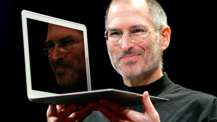 Apple CEO Steve Jobs holds up the new MacBook Air on