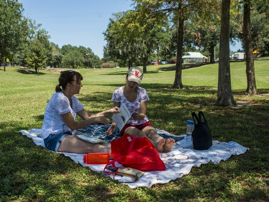 Nola Brennan and Sophie Larson read magazines under a tree in Girard Park in Lafayette.