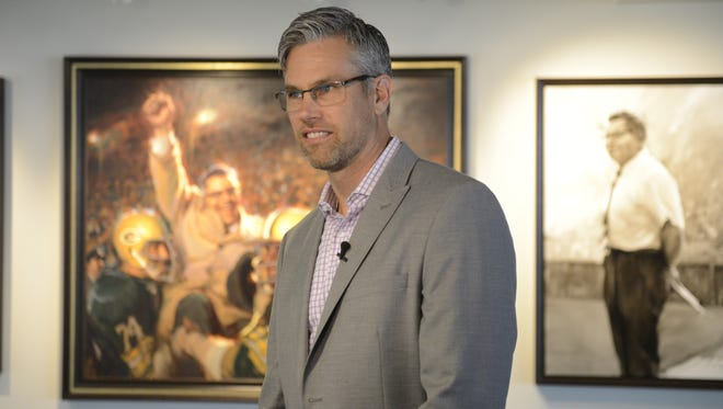 Dan Gerhartz of Kewaskum stands in front of his painting of Vince Lombardi and the victorious Green Bay Packers that is part of more than 500 pieces of art added to Lambeau Field's suite and club seat areas.