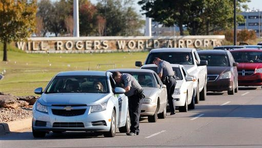 Oklahoma City police officers gather information from vehicles leaving Will Rogers World Airport, Tuesday, Nov. 15 2016, in Oklahoma City. The airport was put on lockdown after a shooting at the main terminal.