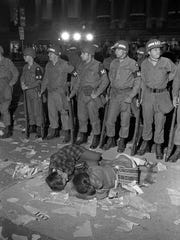 A pair of protesters lie on the ground before a line of National Guardsmen in Chicago during the 1968 Democratic National Convention.