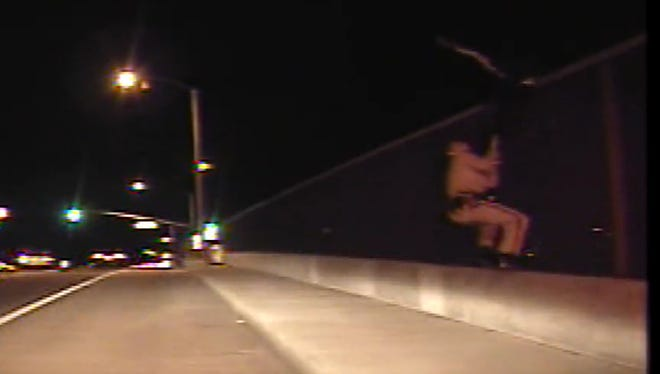 Highway Patrol Officer Dane Norem clings to the legs of a suicidal man on an overpass fence in 2012. The man, Javier Hernandez, slashes down at Norem with a knife.
