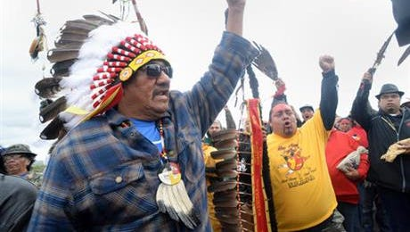 JR American Horse, left, raises his fist with others while leading a march to the Dakota Access Pipeline site in southern Morton County North Dakota. Several hundred protesters marched about a mile up Hwy 1806, Friday Sept. 9, 2016, from the protest camp to the area of the pipeline site where some archaeological artifacts have been discovered.