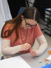Eleventh-grader Grace Wells creates a bracelet. She