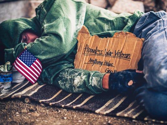 Fighting adversity. Homeless war veteran sleeping with sign and money tin