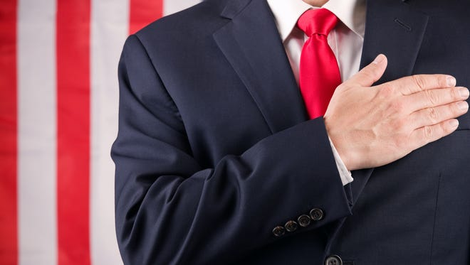 A man in a suit and red tie standing in front of an American flag with his hand on his heart.