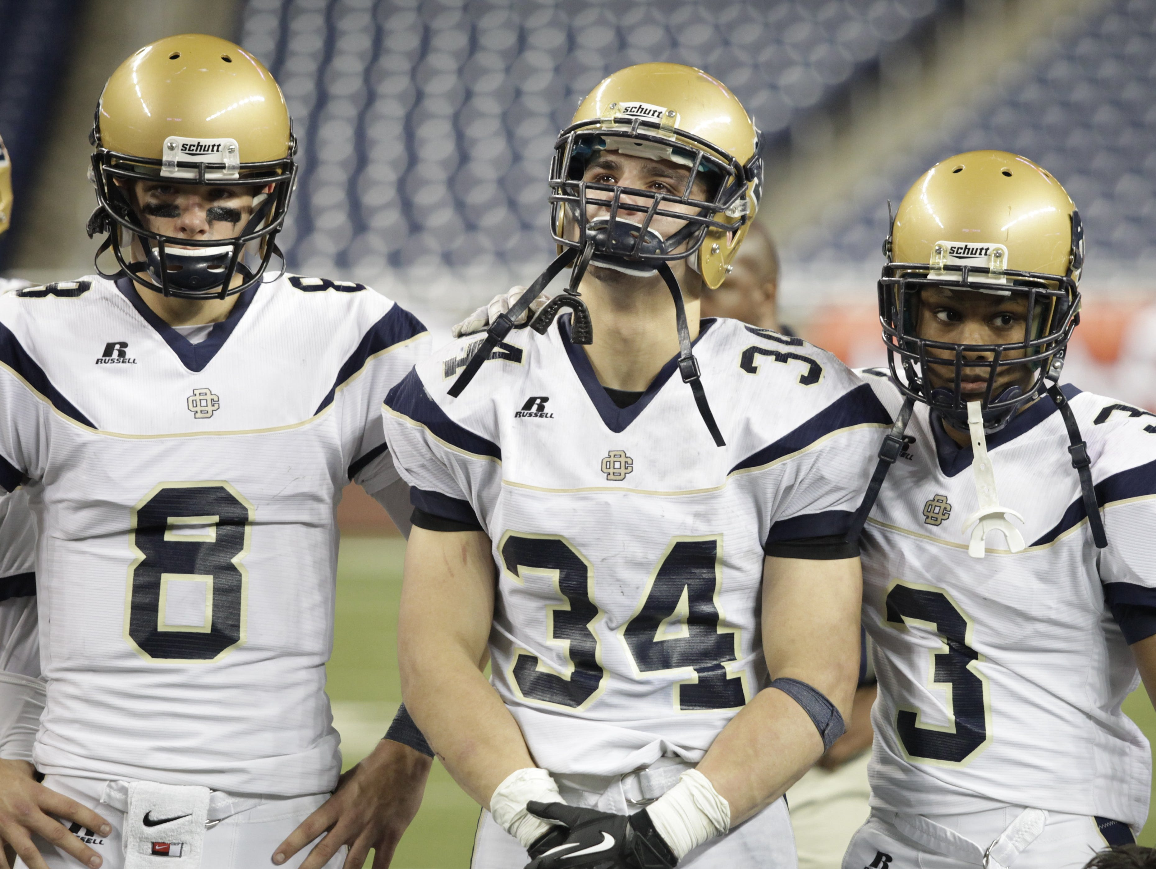 Birmingham Country Day junior quarterback Tyler Wiegers (8), senior fullback Gianmarco Rea (34) and senior defensive back Trevor Woodland (3) console each other after loosing the Division 4 state championship game against Grand Rapids South Christian on Nov. 23, 2012, at Ford Field.
