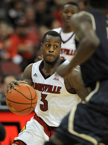 Louisville's Chris Jones (3) drives around FIU's Tashawn