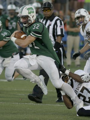 Badin's Cody Boxrucker drags Roger Bacon's Nahshon Walker during the Rams' 49-13 win on Saturday.