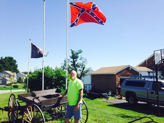 "Steve Elliott, 61, stands by his Confederate flag on Windsor Road in Windsor Township on Wednesday morning. Elliott said he sees the flag as a symbol of his heritage - his family is from West Virginia - not as one of slavery. To blame the flag on the recent massacre at a southern black church is ""ridiculous,"" Elliott said. ""If somebody's nuts, they're nuts,"" he said."