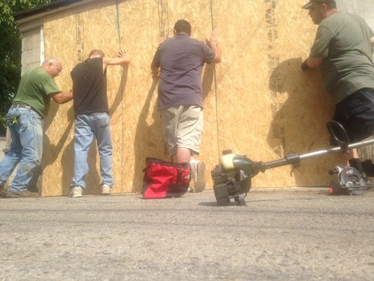 From left to right, Dave Wisner, Brian Hubler, Jason Cottrill and Brandon Hershey press plywood against the garage behind 218 Walnut St. in York. The crew cleaned the garage Thursday morning. Photo by Mark Walters