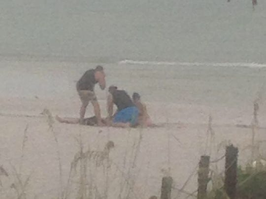 Bystanders tend to Zachary Latawiec (on ground) and Chelsea Gill (seated at far right) after the couple was hit by lighting July 22 on Fort Myers Beach.