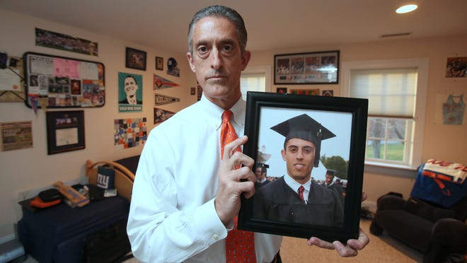 Rich Klein holds a photo of his son Jeff at his Chappaqua home April 15, 2015. He lost Jeff to suicide in 2010.