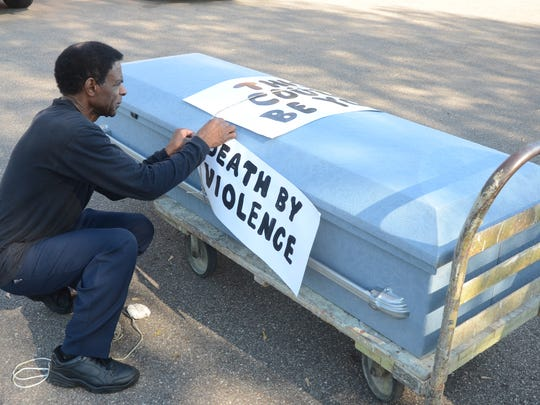 Bobby Holley placed signs of 'death by violence' and 'this could be you' on the casket.