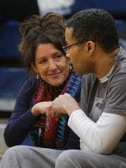 Cindi Gonzalez-Cosby fist-bumps her husband, Dr. ChrisCosby, during a University High game.