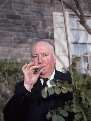 Alfred Hitchcock standing next to a bush in Hollywood, California in 1964.