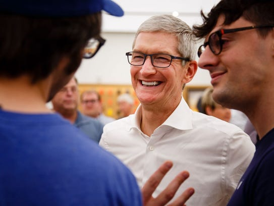 Apple CEO Tim Cook talks with employees on a visit