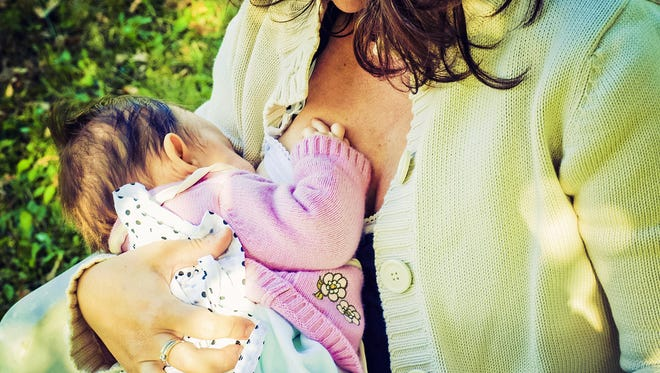 A mother breast feeds a baby.