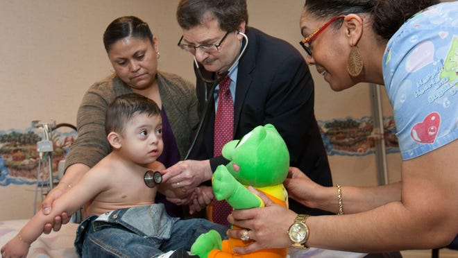 Dr. Mitchel Alpert, a pediatric cardiologist in Brick, examines 22-month-old Drake Vargas, Lakewood, while Vargas' mother Ana Perez (top left) and medical assistant Melissa Ynoa (right) look on.