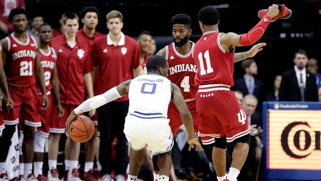 Indiana guard Devonte Green (11) holds his shoe on his hand while guarding against Seton Hall guard Khadeen Carrington (0) during the first half of an NCAA college basketball game, Wednesday, Nov. 15, 2017, in Newark, N.J.