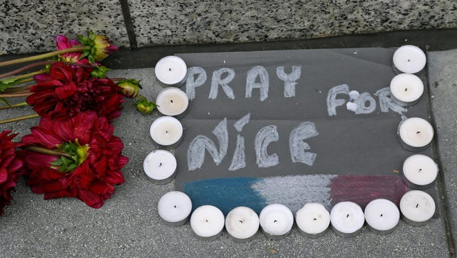 Flowers and candles are left following the attacks in Nice outside the entrance to the French Consulate Friday, July 15, 2016, in San Francisco.  Scores of people were killed Thursday night after a Tunisian man drove a truck through crowds celebrating Bastille Day in Nice.