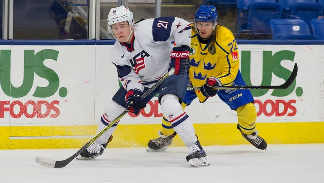 USA White Team forward Ivan Lodnia (21), of Novi, fends off a check from Team Sweden's Axel Jonsson Fjallby (22) during Sunday's game at USA Hockey Arena in Plymouth.
