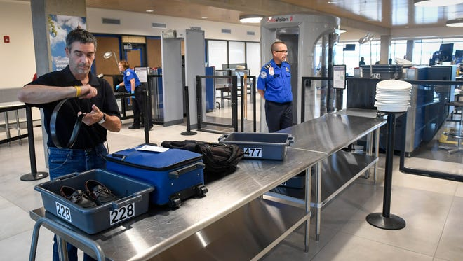 Air passenger Rick Buffalini prepares his belongings for scanning as he passes through the new Transportation Security Administration screening line that's a key part of the terminal renovation project at Evansville Regional Airport Tuesday, July 18, 2018.