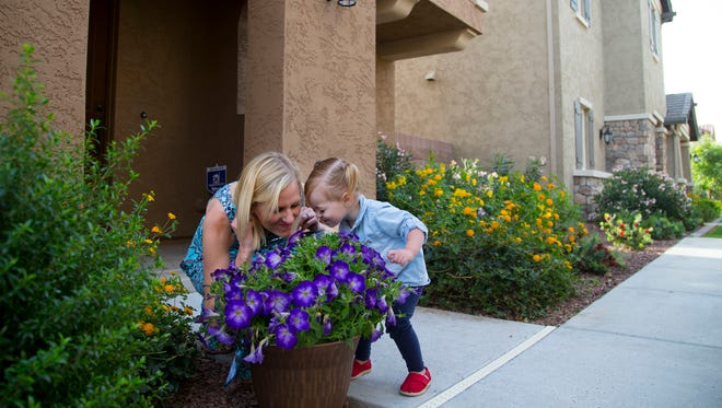 Kristin Seed and her daughter Sloane smell flowers outside their Gilbert home on April 4, 2015.