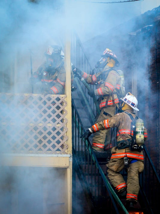 Firefighters battle a multi-building row home blaze in the 300 block of E. Poplar St. in York City, Wednesday Oct. 20, 2015.  John A. Pavoncello - jpavoncello@yorkdispatch.com