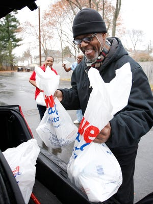 Charles Hampton loads turkeys in his trunk as he gets ready to make deliveries to residents on the east side of Elmira on Thursday.