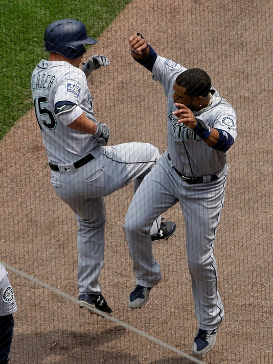 Seattle Mariners' Kyle Seager, left, celebrates with Robinson Cano after hitting a solo home run against the Chicago White Sox during the fourth inning of a baseball game, Sunday, July 16, 2017, in Chicago. (AP Photo/Nam Y. Huh)