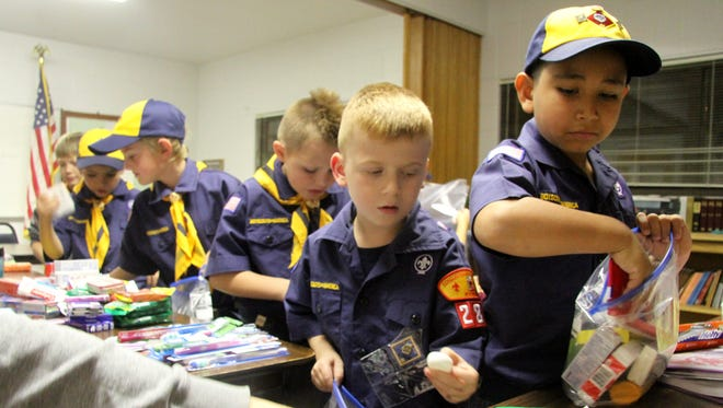 Members of Boy Scout Pack 286 put together care packages for overseas troops on Monday night.