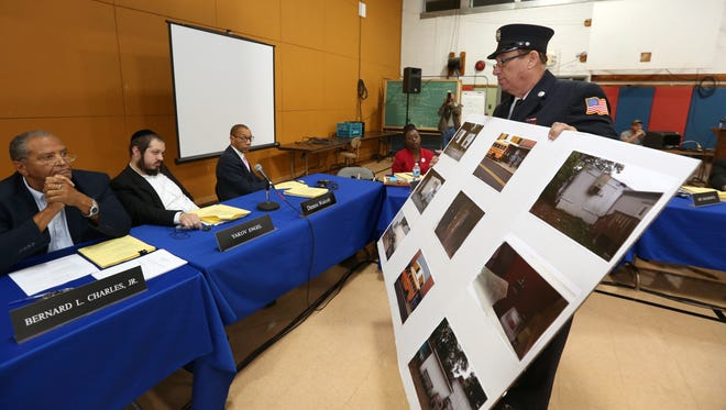 Cpt. Justin Schwartz of the Spring Valley Fire Dept and a member of the illegal housing task force presents photos of fire violations at yeshivas during a meeting of the East Ramapo School Disttrict board at district headquarters in Chestnut Ridge Oct. 13, 2015.