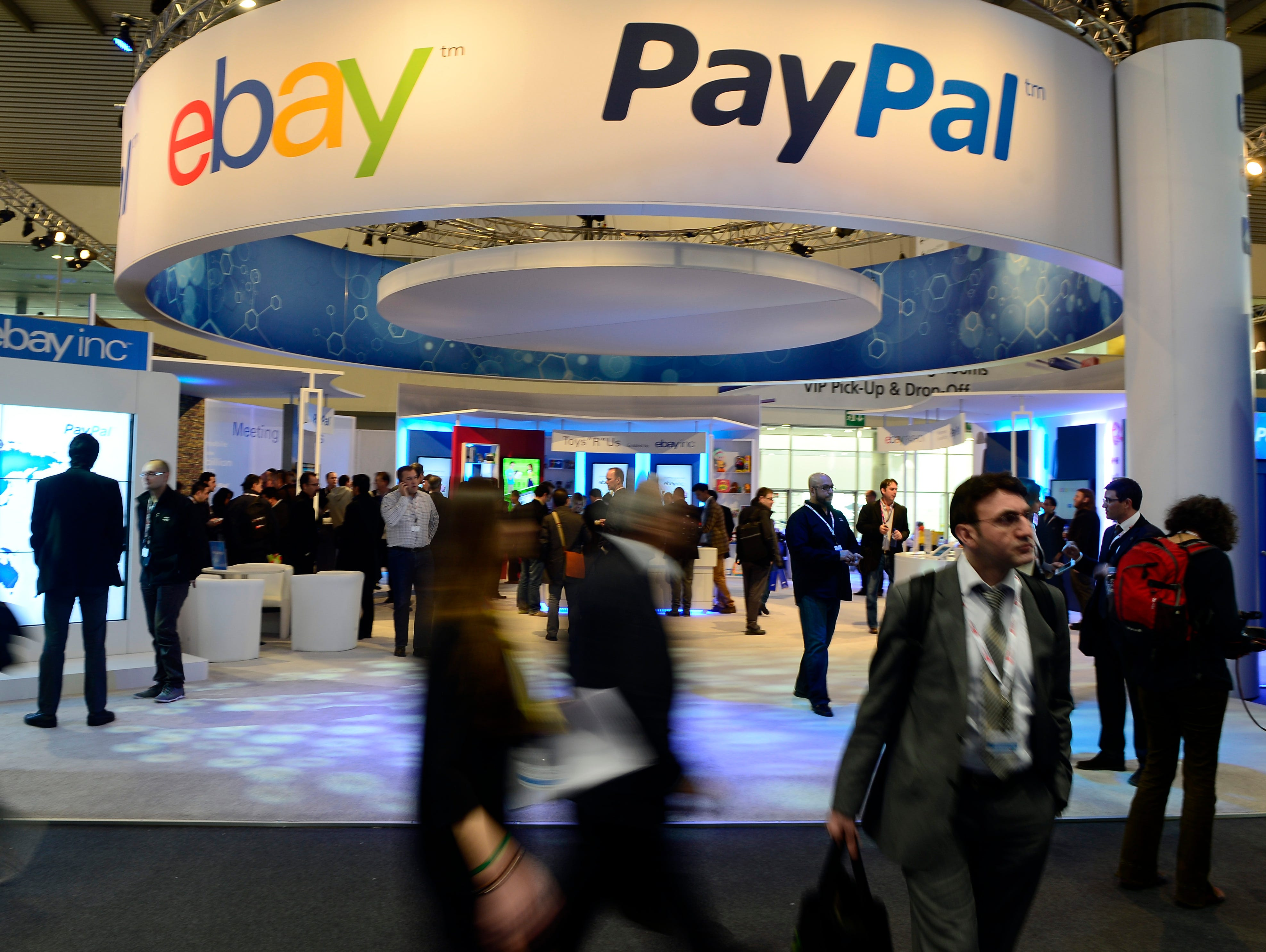 Attendees walk in front of an EBay and PayPal display area at the Mobile World Congress in 2013, the world's largest mobile phone trade show, in Barcelona, Spain.