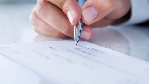 Stock image of someone writing a check